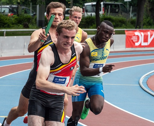 relay runner passing the baton to the teammate following him