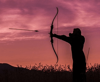 an archer shooting an arrow from a bow at twilight