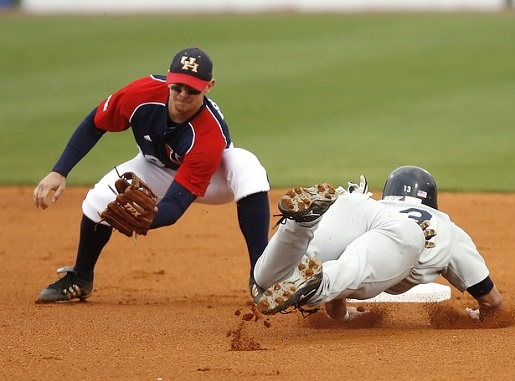 a runner sliding into 2nd base as the 2nd baseman tries to catch the ball
