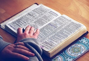 a person's hand resting on n open Bible