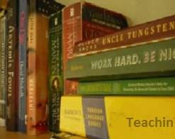 a bookshelf with books standing and textbooks in a pile next to them