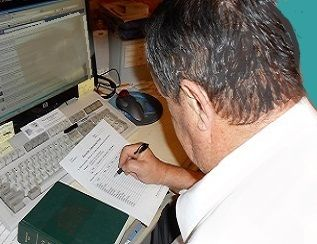 class preparation: man taking notes while using a book and computer.