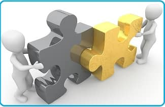 cooperation: two 3-dimensional figures of people fitting two puzzle pieces together