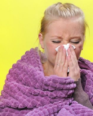 A lady in a blanket sneezing into a tissue.