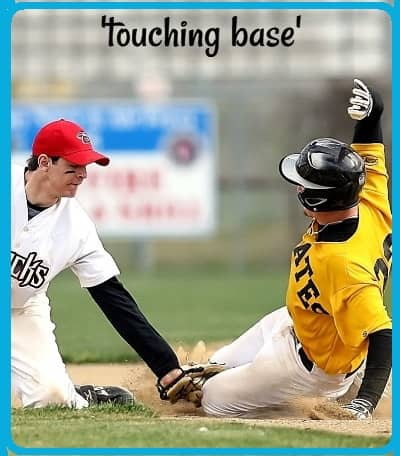 Baseball photo: a baseman touches a runner with the ball in his glove as the runner slides into a base. (The runner is 'touching base,' as the caption says.)