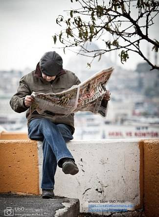 man sitting on a wall reading the news.