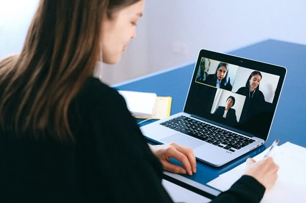 Professional woman attending a virtual meeting on her computer & taking notes