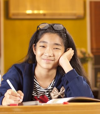 smiling girl completing a reading comprehension worksheet.