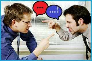 2 men having a fierce argument, pointing their fingers at each other. The man on the left has a red speech bubble above his mouth. The man on the right has a blue one.
