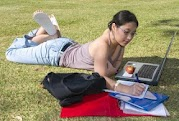 a young woman studying on her computer on the grass