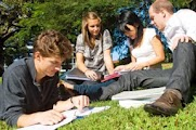 Students studying together on the grass at a university