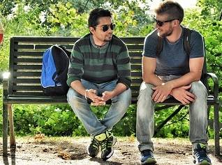 2 men sitting on a park bench and talking.