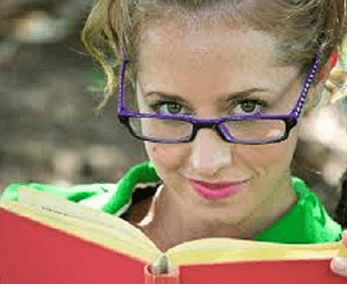 Woman looking up from the book she is reading.